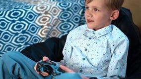 Мальчик играя с собакой в доме на couchHands держа регулятор игры пока ребенок мальчика играя игру по телевизору в комнате видеоматериал