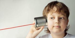 Мальчик играя с телефоном жестяной коробки Изолировано на серой предпосылке стоковые фотографии rf