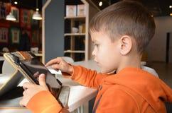 Мальчик играя таблетку в кафе улицы весной стоковые фотографии rf