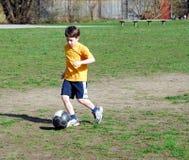 мальчик играя футбол Стоковая Фотография