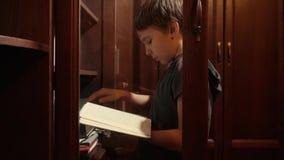 Мальчик идет через книги на полке и выборе одном видеоматериал