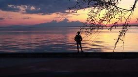 Мальчик идя на пляж с взглядом пинка и желтого захода солнца на заднем плане акции видеоматериалы