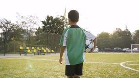 Мальчик идя с футбольным мячом в руке сток-видео