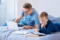 Мальчик изучая пока его отец работая на компьтер-книжке Стоковые Изображения RF