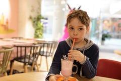 Мальчик имеет milkshake стоковое изображение