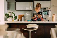 Мальчик имея потеху делая печенья с матерью стоковые фото