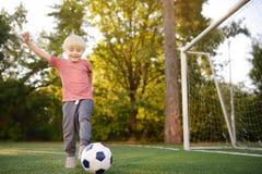 Мальчик имея потеху играя футбол/футбольную игру на летний день Active игра/спорт outdoors для детей стоковые фото