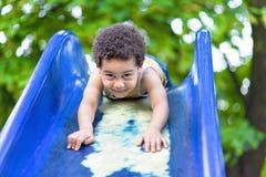 Мальчик имея потеху на спортивной площадке outdoors в лете Стоковая Фотография RF