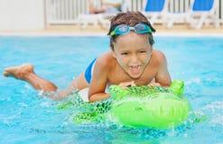Мальчик имея потеху с раздувной игрушкой в бассейне Стоковое Изображение RF