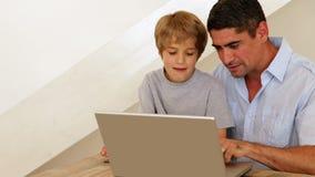 Мальчик используя компьтер-книжку с его отцом на таблице Стоковое Изображение