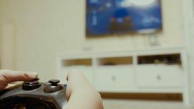 Мальчик используя регулятор для того чтобы сыграть видеоигру стоковое изображение rf