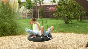 Мальчик и девушка, близнецы отбрасывая на качании гамак на парке атракционов в городе 4k, космос экземпляра сток-видео