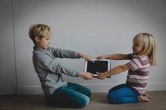 Мальчик и девушка воюя для сенсорной панели, наркомании компьютера стоковые фото