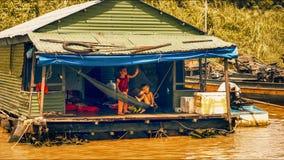 Мальчик и девушка говорят здравствуйте! к туристам на озере сок Tonle Стоковая Фотография