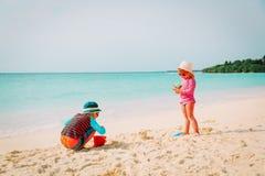 Мальчик и девушка играют с песком на пляже Стоковое фото RF