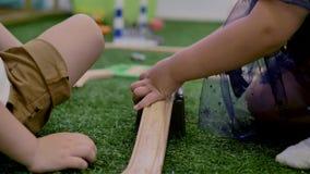 Мальчик и девушка, играющ на пластиковой игрушке, сидя на зеленой искусственной траве в комнате видеоматериал