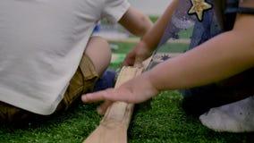 Мальчик и девушка, играющ на пластиковой игрушке, сидя на зеленой искусственной траве в комнате сток-видео