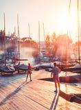 Мальчик и девушка играя бадминтон на пристани на заходе солнца Стоковые Фото