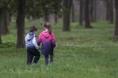Мальчик и девушка идя совместно и держа руки Стоковые Фотографии RF