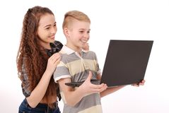 Мальчик и девушка используя изолированную компьтер-книжку Стоковая Фотография