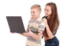 Мальчик и девушка используя изолированную компьтер-книжку Стоковое Изображение