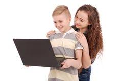 Мальчик и девушка используя изолированную компьтер-книжку Стоковые Фотографии RF