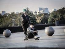 Мальчик и девушка катаясь на коньках на одиночном скейтборде стоковая фотография rf