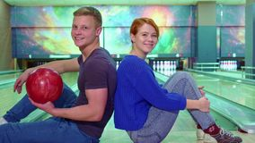 Мальчик и девушка показывают их большие пальцы руки вверх на боулинге стоковое фото rf