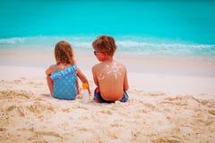 Мальчик и девушка предохранения от Солнця с suncream на пляже Стоковые Изображения