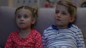 Мальчик и девушка смотря ТВ вечером, вспугнутый когда родители внезапно возвратят домой акции видеоматериалы