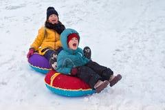 Мальчик и девушка sledding от горы эмоциональный радостные и многолетние брат и сестра тратят совместно в зиме стоковая фотография