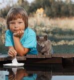Мальчик и его любимый котенок играя с шлюпкой от пристани в пруде стоковые фото