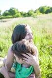 Мальчик и его мать лежат в луге Стоковые Изображения