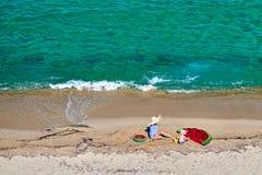 Мальчик и его мать на пляже с раздувным поплавком стоковое изображение