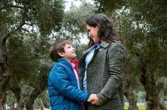 Мальчик и его мать смотрят один другого и смеются над стоковое изображение