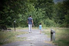 Мальчик и его отец наслаждаясь теплым летним днем Родитель и зрачок идя к детскому саду preschool Активная семья идя внутри стоковое фото rf