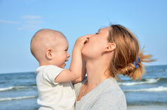 Мальчик и его потеха матери на пляже Стоковая Фотография