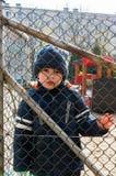 Мальчик и загородка решетки Стоковое Фото