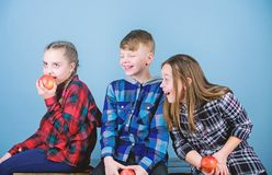 Мальчик и подруги едят закуску яблока пока ослабляющ Здоровое питание dieting и витамина Концепция закуски школы Группа стоковая фотография rf