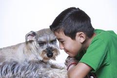 Мальчик и собака положили их головы совместно Стоковое Изображение
