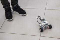Мальчик и собранная модель робота в лаборатории нанотехнологии стоковое фото rf