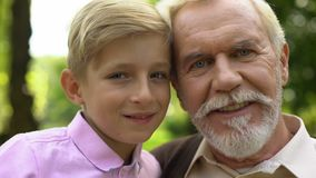 Мальчик и старик представляя для камеры, усмехающся, доверяющ отношениям с дедом сток-видео