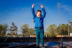 Мальчик и фонтан брызга стоковые фото