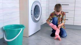 Мальчик кладет на резиновые перчатки для того чтобы очистить пол кухни Обязанности ребенка домашние сток-видео