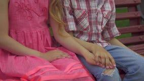 Мальчик кладет руку девушек на его колено на стенде сток-видео