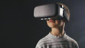 Мальчик конца-вверх 10 лет используя шлем виртуальной реальности Ребенок получая опыт в использовании VR 360 видеоматериал