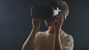Мальчик конца-вверх 10 лет используя шлем виртуальной реальности Ребенок получая опыт в использовании VR 360 сток-видео