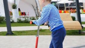 Мальчик крупного плана едет самокат вдоль парка развлечений сток-видео