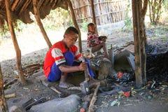 Мальчик кузнеца бить молотком молотком и создавая сувениры для туристов стоковые изображения rf