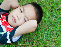 мальчик лежа на зеленой траве Стоковые Изображения RF